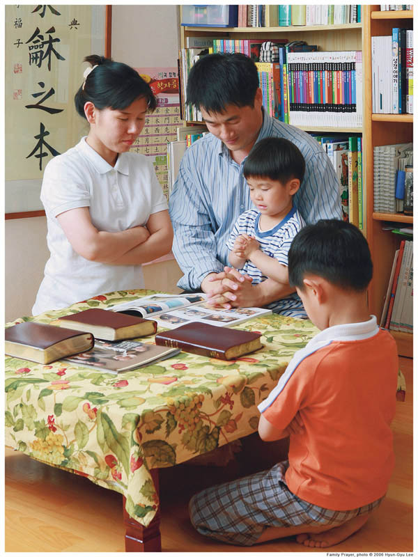 Tradional families provide the best outcome for children. Mother, father, children praying.