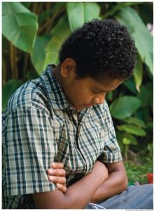 Prayer is one way to know God better. Boy praying.