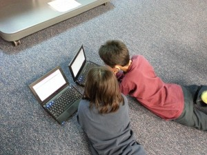 two children watching movies on computers