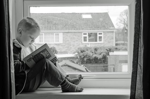 homeschooler reading in window seat