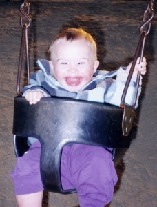 Jane's son, who has Down Syndrome, in a baby swing