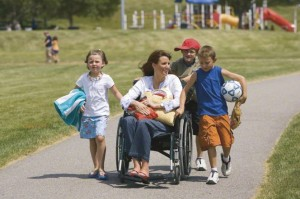 Mother in wheelchair at park with children