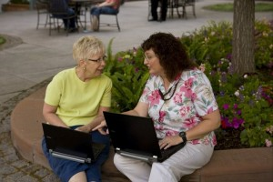 Two women indexing on laptops at a park