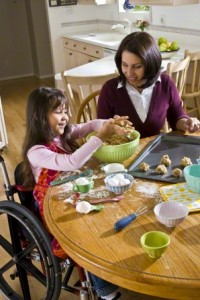 girl in wheelchair baking with mother