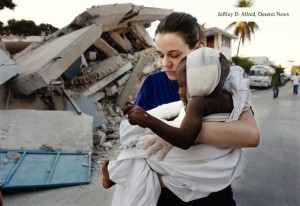 woman carrying injured child in Haiti after earthquake