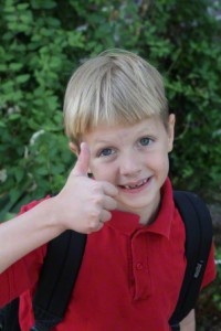 Boy with backpack giving thumbs up