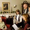 People singing Christmas carols to an elderly woman
