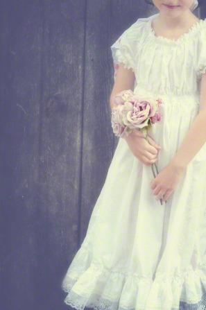 Little girl in long white dress holding flowers