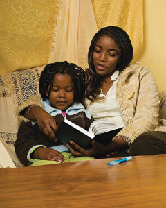 Black mom and daughter reading