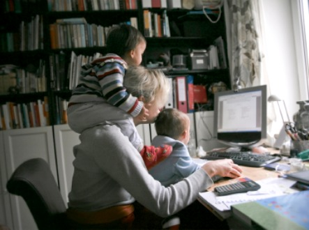 mom working at computer with toddlers hanging on