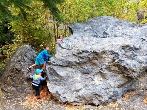 Jake, Bratcher, and Emilia climbing rocks