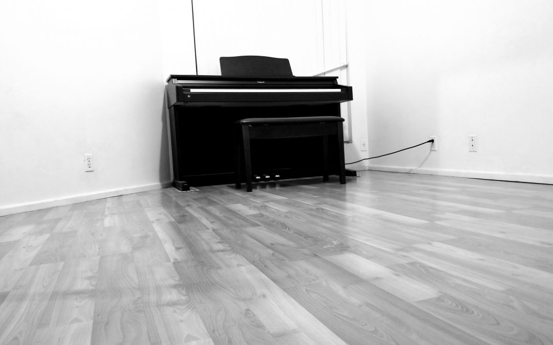 still black and white picture of a piano sitting alone in an empty room