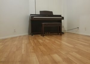 electric upright piano standing still alone in a room